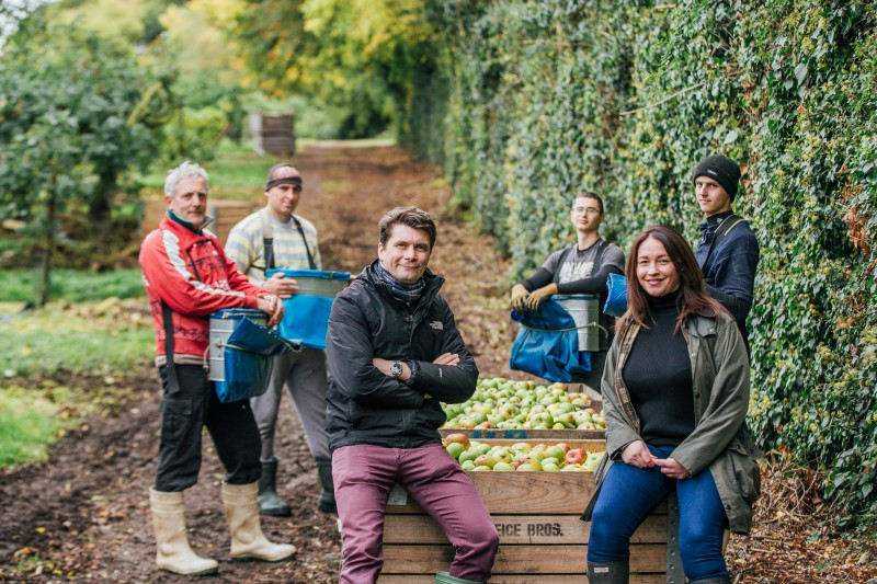 Fifth generation apple grower Greg MacNeice of Mac Ivors Cider Co with journalist Eleanor McGillie with Polish apple pickers in MacNeice's orchards in Co Armagh. MGMPR_01